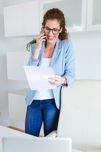 Kobieta stoi podczas rozmowy telefonicznej w pracy