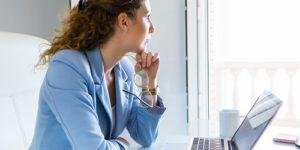 Kobieta siedzi w pracy przed laptopem