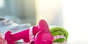 Dwa różowe ciężarki, zielony ręcznik i taśma krawiecka obrazują zdrowe nawyki