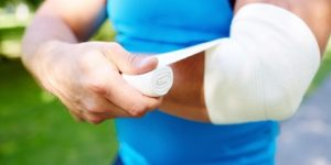 Mężczyzna robi opatrunek na łokciu bandażem elastycznym