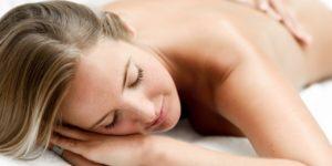 Młoda kobieta leży na brzuchu w gabinecie masażu leczniczego