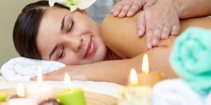Młoda kobieta korzysta z masażu przy blasku świec i aromaterapii w gabinecie SPA