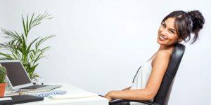 Kobieta siedzi oparta o oparcie fotela biurowego