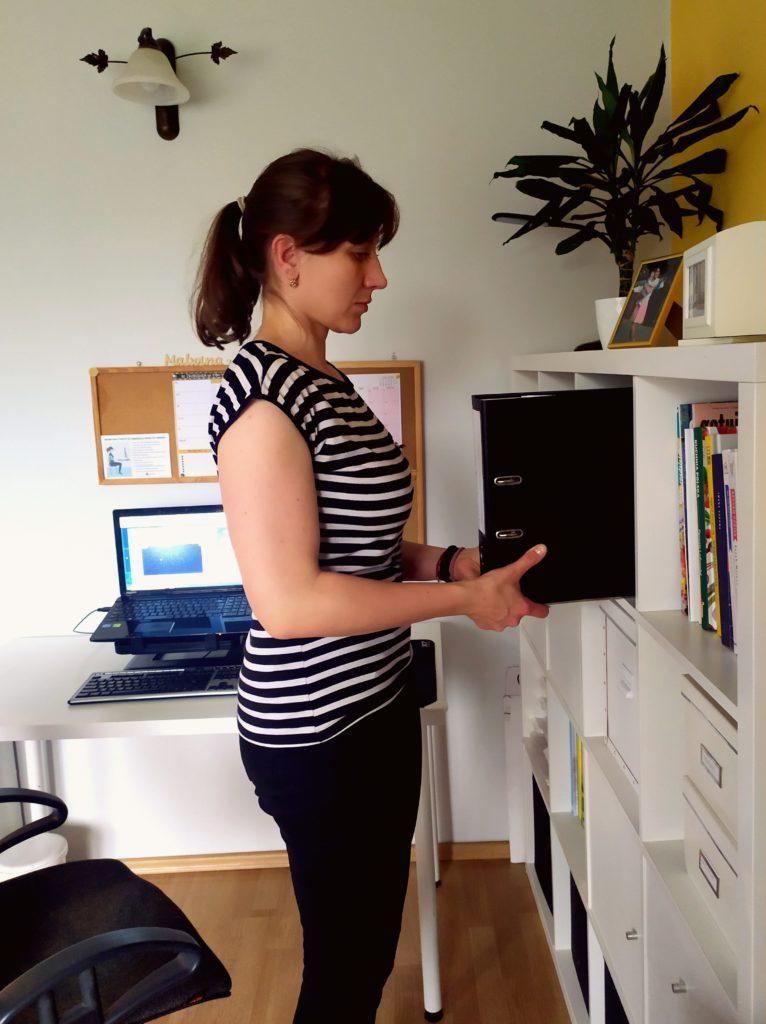 Kobieta zdejmuje segregatory z półki stojąc przodem do niej