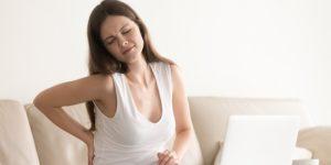Kobieta masuje bolące plecy i siedzi przy komputerze